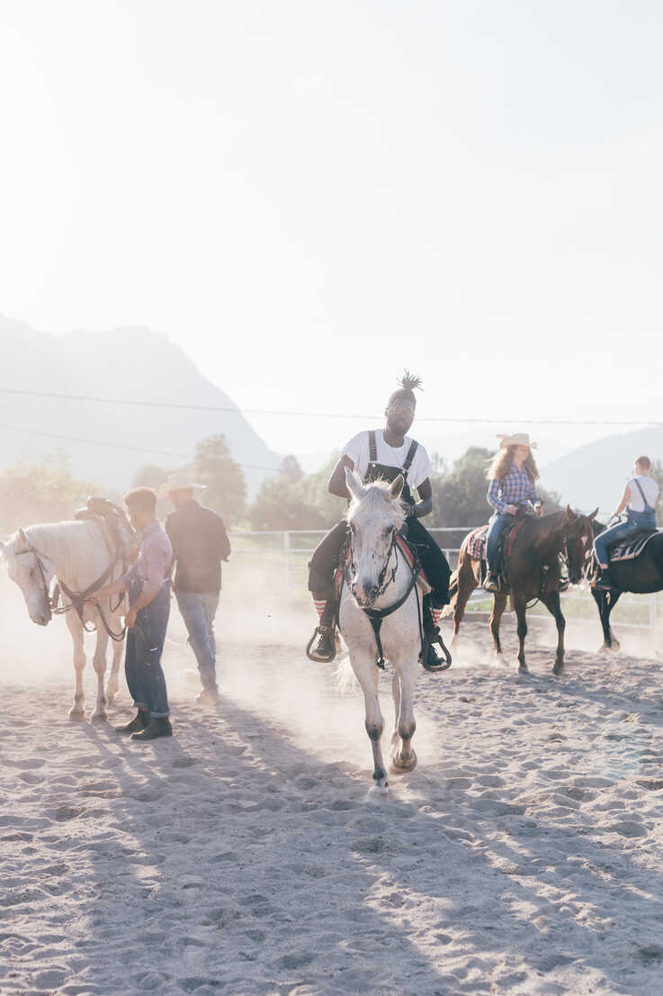 Young hipster man with friends riding horses in rural equestrian arena, Primaluna, Trentino-Alto Adige, Italy - CUF47505 - Eugenio Marongiu/Westend61