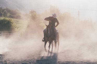 Cowboy horse riding in dusty equestrian arena, Primaluna, Trentino-Alto Adige, Italy - CUF47508