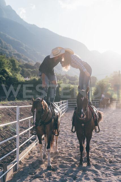Cowgirl and boyfriend standing on horseback kissing in equestrian arena, Primaluna, Trentino-Alto Adige, Italy - CUF47511 - Eugenio Marongiu/Westend61