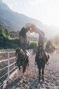 Cowgirl and boyfriend standing on horseback kissing in equestrian arena, Primaluna, Trentino-Alto Adige, Italy - CUF47511