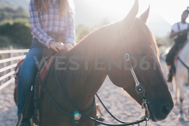 Man and woman on horseback in rural equestrian arena, cropped - CUF47514