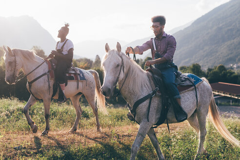 Two young men horse riding in field, Primaluna, Trentino-Alto Adige, Italy - CUF47517