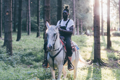 Cool young man horse riding in sunlit forest,  Primaluna, Trentino-Alto Adige, Italy - CUF47520