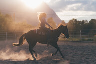Long haired young woman cantering on horse in rural equestrian arena, backlit, Primaluna, Trentino-Alto Adige, Italy - CUF47523