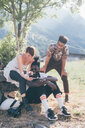 Three young adult hikers in field looking at smartphone, Primaluna, Trentino-Alto Adige, Italy - CUF47529