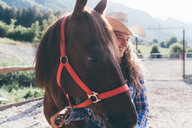 Young cowgirl leading horse in rural equestrian arena - CUF47532