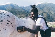 Cool young man grooming horse in rural equestrian arena, Primaluna, Trentino-Alto Adige, Italy - CUF47538