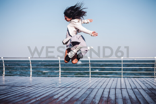 Mid adult woman jumping mid air on sea pier, Odessa, Odeska Oblast, Ukraine - CUF47541