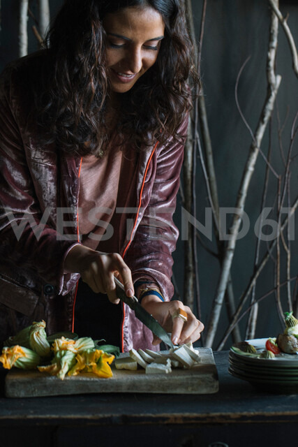 Young woman chopping fresh food on rustic cutting board - CUF47544