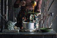 Young woman ladling fresh soup from saucepan at rustic kitchen counter, mid section - CUF47547