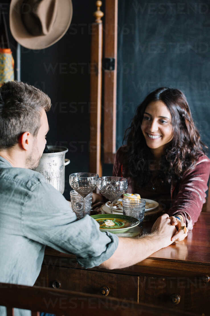 Romantic young couple having a meal, holding hands across table - CUF47553 - Alberto Bogo/Westend61