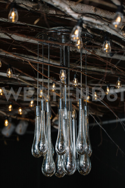 Retro decorative lights and glass chandelier hanging from rustic ceiling - CUF47556