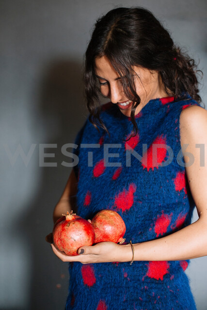 Young woman in red patterned dress holding pomegranates - CUF47568