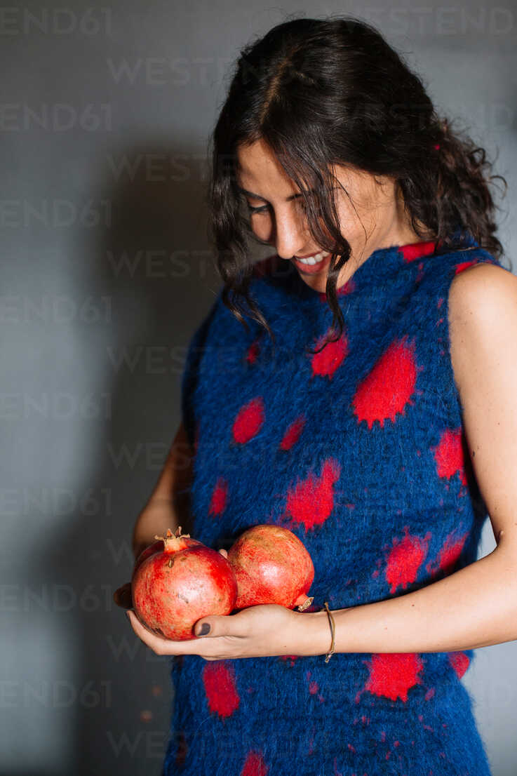 Young woman in red patterned dress holding pomegranates - CUF47568 - Alberto Bogo/Westend61