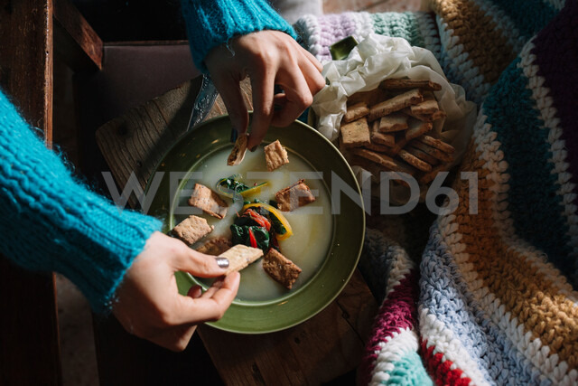 Young woman placing savoury biscuits in bowl of fresh food - CUF47571 - Alberto Bogo/Westend61