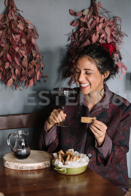 Young woman at rustic table holding glass of red wine - CUF47574 - Alberto Bogo/Westend61