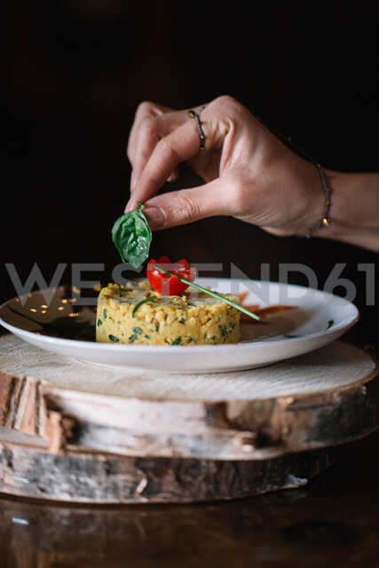 Young woman putting basil garnish on food, close up of hand - CUF47577 - Alberto Bogo/Westend61