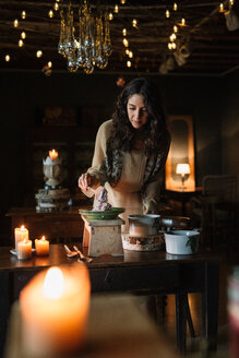 Young woman at vintage table serving risotto - CUF47580