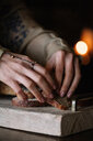 Young woman preparing brown bread on rustic chopping board, close up of hands - CUF47583