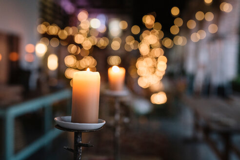 Close up of lit candle in cafe with decorative lights - CUF47586