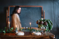 Young woman moving past vintage dinner table with candles and bowl of globe artichokes - CUF47589
