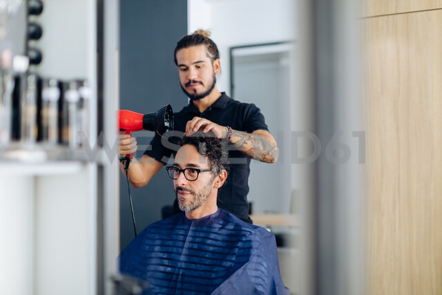 Male hairstylist blow drying male customer's hair in hair salon - CUF47598 - Sofie Delauw/Westend61