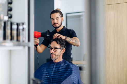 Male hairstylist blow drying male customer's hair in hair salon - CUF47598