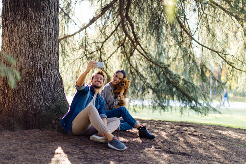 Couple with pet dog sitting by large tree - CUF47613