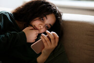 Teenage girl lying on sofa in dark reading text message - CUF47673