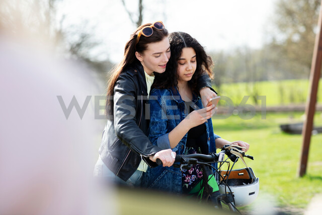 Teenage girls reading text together on push bike - CUF47682