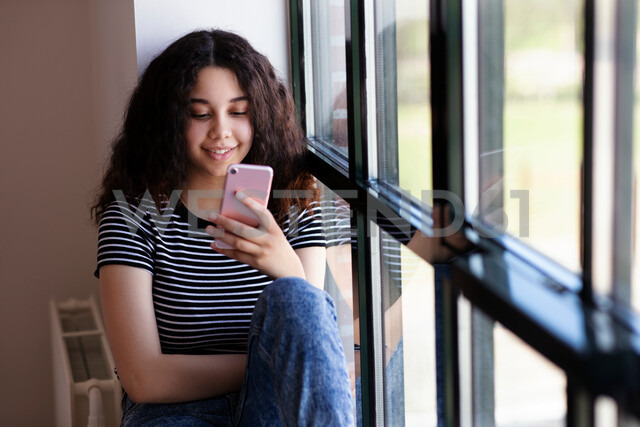 Teenage girl reading text message on cellphone by glass window - CUF47688