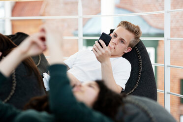 School friends lying on beanbags and texting at school - CUF47691