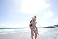 Sisters playing piggyback on beach - CUF47715