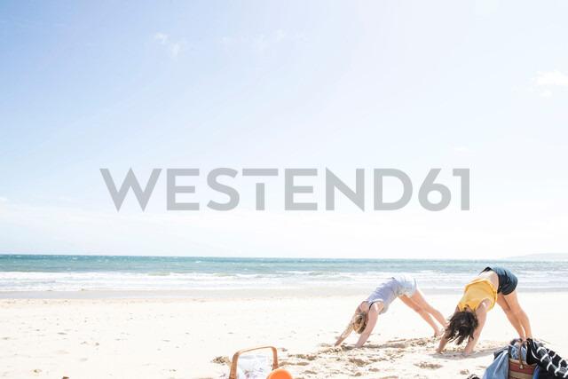 Sisters enjoying yoga on beach - CUF47718