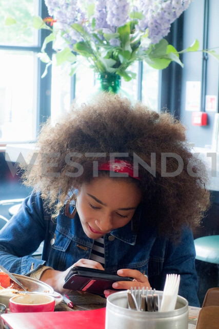 Woman using cellphone in cafe, London, UK - CUF47748