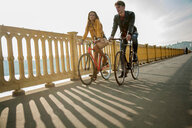 Couple crossing bridge on bicycles, Budapest, Hungary - CUF47775