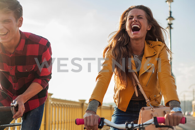Couple crossing bridge on bicycles, Budapest, Hungary - CUF47781