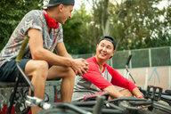 BMX cyclists resting beside ramp - CUF47799