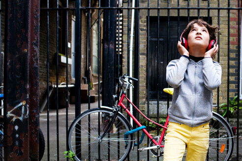 Boy listening to music with headphones, bicycle in background - CUF47817