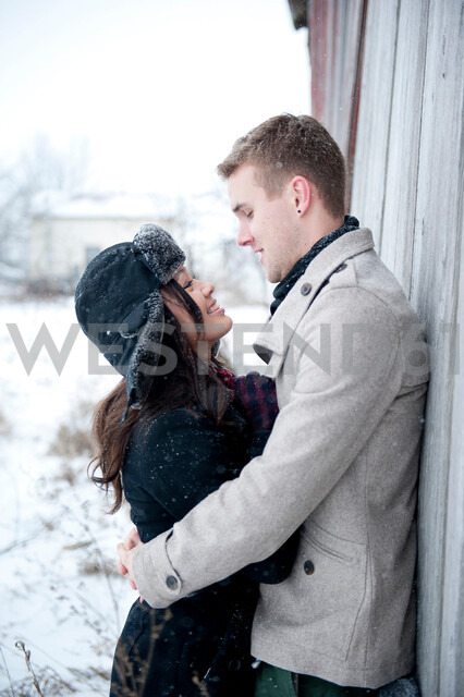 Young couple hugging against cabin in snow - CUF47820