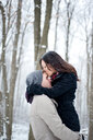 Romantic young woman kissing boyfriend's forehead in snow covered forest, Ontario, Canada - CUF47823