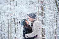 Romantic young couple face to face in snowy forest, Ontario, Canada - CUF47826