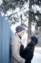 Young couple hugging against fence in snow - CUF47829