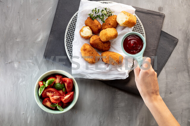 Placing tomato sauce on plate with potato croquettes, cropped overhead view of hand - CUF47835