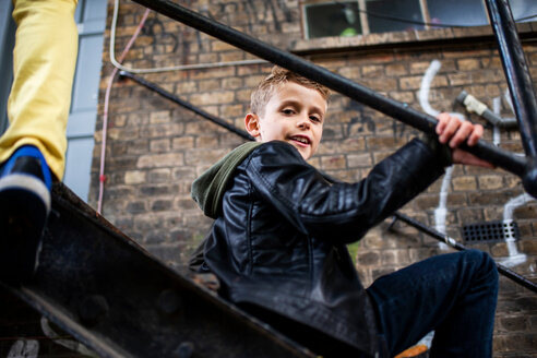 Boy sitting on metal staircase - CUF47841
