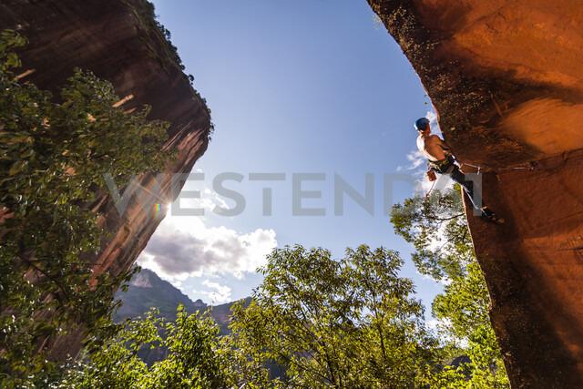 Rock climber scaling rock face, Liming, Yunnan, China - CUF47844