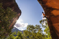 Rock climber scaling rock face, Liming, Yunnan, China - CUF47844