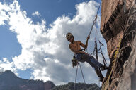Rock climber scaling rock face, Liming, Yunnan, China - CUF47850
