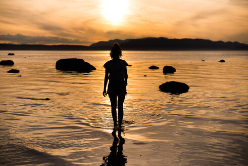 Young woman looking out at sunset, silhouetted rear view, Quadra Island, Campbell River, Canada - CUF47862