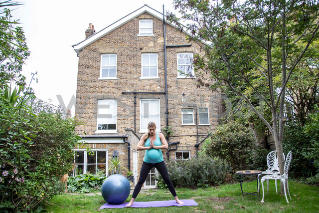 Pregnant mid adult woman practicing yoga in garden - CUF47877